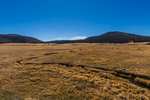 San Antonio Creek running through the vast grasslands of Valles Caldera National Preserve, a National Park Service preserve, with smoke rising from a prescribed burn in the distance,  in northern New Mexico, USA