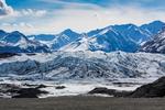 Snow-capped Chugach Mountains rise dramatically behind the terminus of the Matanuska Glacier, northeast of Anchorage, Alaska, USA