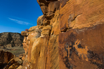 Petroglyphs of a game animal, an elk or bighorn sheep, and a cross, on a cliff high above Nine Mile Canyon, Utah, USA
