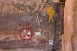 Fremont Culture pictographs, depicting a sun symbol, a human figure, and bighorn sheep in red, white, and ochre colors, Nine Mile Canyon, Utah, USA