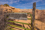 Gate marking the boundary between BLM and national park land along the trail down into Horseshoe Canyon in Canyonlands National Park, Utah, USA