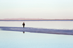 Woman walking on a spit of land extending out into shallow salt water at the Bonneville Salt Flats, in BLM's Special Recreation Management Area west of the Great Salt Lake, Utah, USA