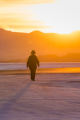 Woman walking into the sunset on the Bonneville Salt Flats, which is BLM land west of the Great Salt Lake, Utah, USA
