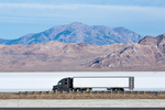 Semi truck traveling west on I-80 across the Bonneville Salt Flats, viewed from the Wendover Salt Flats Rest Area, Utah, USA