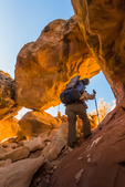 Hiker climbing a route through a sandstone fin within Salt Creek Canyon in The Needles District of Canyonlands National Park, Utah, USA