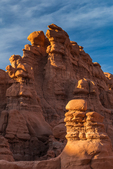 Goblins or hoodoos eroded from Entrada Sandstone, illuminated by sunset light, in Goblin Valley State Park, Utah, USA
