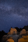 Goblins or hoodoos eroded from Entrada Sandstone, photographed at night with the stars and Milky Way overhead, in Goblin Valley State Park, Utah, USA