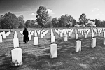 Woman in black walking among gravestones at Fort Custer National Cemetery, a national cemetery where military veterans are buried, near Augusta and Battle Creek, Michigan, USA, 2008_MI_3479