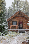 Rob Garrison standing on the porch of Forget_Me_Not Hut (with its short door), one of the Naiset Huts, in a snowstorm, near Mount Assiniboine Lodge; Mount Assiniboine Provincial Park, British Columbia, Canada, Mount_Assiniboine_Naiset_Huts-49