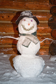 "Snowman (snowwoman) named ""Hippy Chick"" on the porch of one of the Naiset Huts; Mount Assiniboine Provincial Park, British Columbia, Canada, Mount_Assiniboine_Snowman-1"