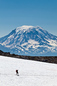 Hiker on the Pacific Crest Trail crosses a remnant snowfield below Old Snowy, with Mount Adams towering behind, in the Goat Rocks Wilderness, Mt. Gifford Pinchot National Forest, Cascade Mountains, Washington State, USA, September, Goat_Rocks-524