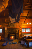 Interior of the Elizabeth Parker Hut, with wood fire blazing and drying out gear, in the Lake O'Hara area of Yoho National Park, British Columbia, Canada, Elizabeth_Parker_Hut-17