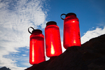 Red water bottles line up on a rock at timberline with the sun shining through, Royal Basin, Olympic National Park, Washington State, USA.
