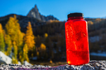 Water bottle with a lot of ice from a cold night camping in The Enchantments, with Prusik Peak distant, Cascade Range, Okanogan-Wenatchee National Forest, Washington State, USA