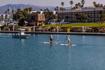 A couple and their dog doing stand up paddle boarding in Channel Islands Harbor as a harbor patrol boat passes, Oxnard, California, USA [No model release; available for careful editorial licensing only]