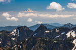 Looking over jagged peaks of the eastern Olympic Mountains toward Mount Rainier seemingly floating in the distance; viewed from the slopes of Buckhorn Mountain in the Buckhorn Wilderness, Olympic National Forest, Olympic Peninsula, Washington State, USA