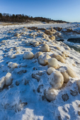 Ice balls formed in the surf, then frozen solid as part of the lake ice at the edge of Lake Michigan in Rosy Mound Natural Area, an Ottawa County Park near Grand Haven, Michigan, USA