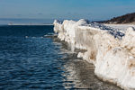 Icicles formed from spray of Lake Michigan waves crashing in against a ridge of ice, with Grand Haven Lighthouse in the distance, viewed from Rosy Mound Natural Area near Grand Haven, Michigan, USA