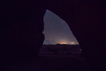 Starry night sky and distant town lights viewed from an arch in the rock formations in City of Rocks State Park, located between Silver City and Deming in the Chihuahuan Desert, New Mexico, USA