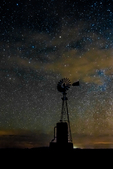 Windmill against vast starry sky, including the Milky Way and wispy clouds, above City of Rocks State Park, located between Silver City and Deming in the Chihuahuan Desert, New Mexico, USA