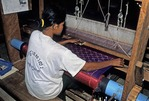 CAMBODIAN STUDENT WEAVING SILK ON A LOOM