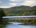 The East Dummerston covered bridge spans the West River in East Dummerston , VT
