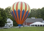 A hot air balloon lands at Marshland Farm at the Quechee Balloon Fest in Quechee, VT