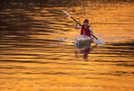 UTAH. USA. Woman paddler in kayak on Green River at sunset. Labyrinth Canyon. Colorado Plateau. Proposed Labyrinth Canyon BLM Wilderness. MR
