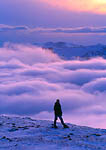 ROCKY MOUNTAIN NATIONAL PARK, COLORADO. USA. Hiker above the clouds on Trail Ridge at dusk. Never Summer Range in distance. Rocky Mountains.