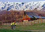 UTAH. USA. Tandem bicyclists & barn in early spring below Wellsville Mountains. Cache Valley.