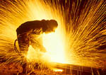 Worker cuts steel with oxygen cutting torch at Nucor Steel mill. Plymouth, UTAH. USA.