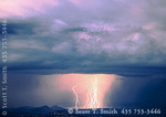UTAH. USA. Multiple cloud-to-ground lightning strokes. Thunderstorm at dusk over Cathedral Valley. View into Capitol Reef National Park from Boulder Mountain.