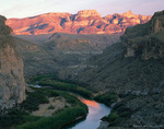 BIG BEND NATIONAL PARK, TEXAS. USA. The Rio Grande at sunset in Boquillas Canyon below Mexico's Sierra del Carmen. Chihuahuan Desert. Mexico on left, USA on right.