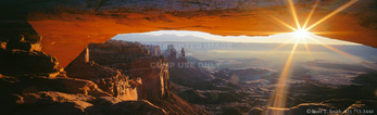 CANYONLANDS NATIONAL PARK, UTAH. USA. Mesa Arch at sunrise. Natural arch overhanging canyon rim. Colorado River canyon in distance. Island in the Sky. Colorado Plateau.