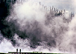 YELLOWSTONE NATIONAL PARK, WYOMING. USA. Steam rises above people on boardwalk. Steam from thermal features in Middle Geyser Basin.