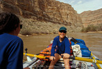 GLEN CANYON NATIONAL RECREATION AREA, UTAH. USA. Smiling young boatwoman rows raft on San Juan River.