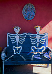 RANCHOS DE TAOS, NEW MEXICO. USA. Skeleton couple, bench outside shop. Rio Grande Valley.