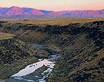South Fork Owyhee River in gorge cut through basalt. Last light of sunset on Bull Run Mountains in distance. Owyhee Desert.