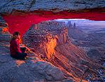 CANYONLANDS NATIONAL PARK, UTAH. USA. Young woman hiker sits below Mesa Arch at sunrise.