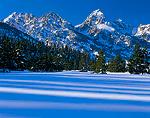 GRAND TETON NATIONAL PARK, WYOMING. USA. Grand Teton in Teton Range above tree shadows on snow.