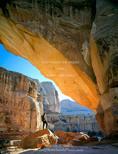 CAPITOL REEF NATIONAL PARK, UTAH. USA. Hiker below Hickman Bridge. Natural bridge formed in Navajo Sandstone.
