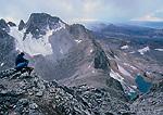 GRAND TETON NATIONAL PARK, WYOMING. USA. Climber takes a break near summit of Middle Teton. South Teton & Alaska Basin in distance. Teton Range.