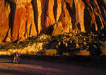 CAPITOL REEF NATIONAL PARK, UTAH. USA. Mountain biker below cliffs of Capitol Gorge.