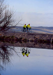 UTAH. USA. Tandem bicyclists reflected in Little Bear River in early spring. Cache Valley.