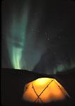 ALASKA. USA. Aurora borealis & the Big Dipper above tent lit by candle. Alaska Range. Along the Delta River. Delta National Wild & Scenic River.