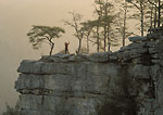 FALL CREEK FALLS STATE PARK, TENNESSEE. USA. Hiker stretches at sunrise above Cane Creek Gorge. Cumberland Plateau.