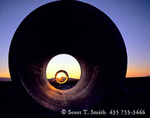 """UTAH. USA. Summer solstice sunrise viewed through the """"Sun Tunnels"""", earth art in the Great Salt Lake Desert. Built by New York artist Nancy Holt, four 22 ton concrete tunnels are aligned with sunrise & sunset on solstices."""