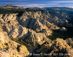 UTAH. USA. Morning light on sandstone cliffs above Death Hollow. View into Box-Death Hollow Wilderness from Antone Bench. Dixie National Forest. Roger Peak & Boulder Mountain in distance.