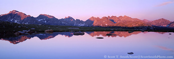 BRIDGER WILDERNESS, WYOMING. USA. Peaks of the Continental Divide reflected in tarn at sunset. Along Fremont Trail. Wind River Range. Bridger-Teton National Forest. Rocky Mountains.