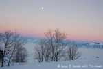 UTAH. USA. Full moon at dusk in winter above maple trees on ridge in Wellsville Mountains. Fog-filled Cache Valley & Bear River Range in distance.